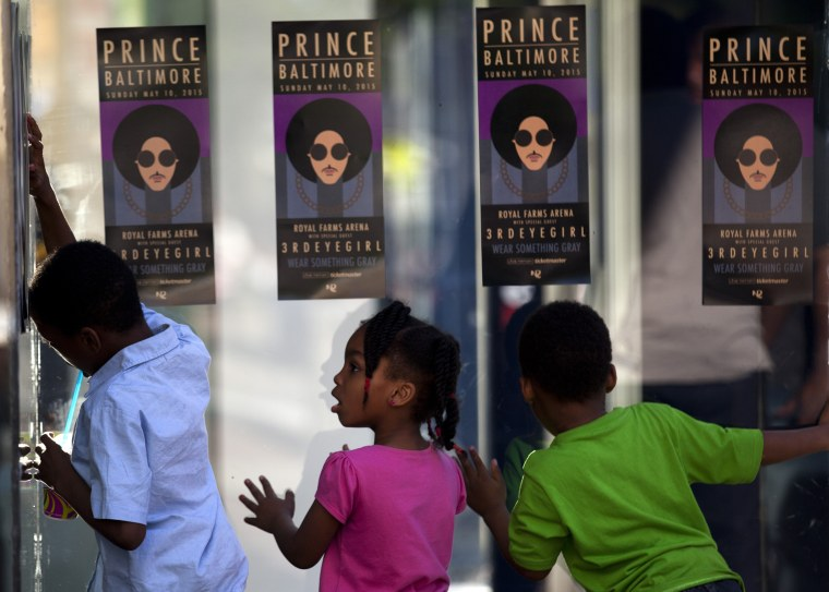 "Children look through glass as fans of musical artist Prince enter a ""Rally 4 Peace"" concert in Baltimore, Maryland on May 10, 2015."