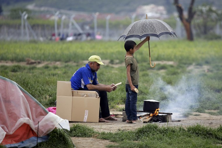 Image: migrants protect fire from rain