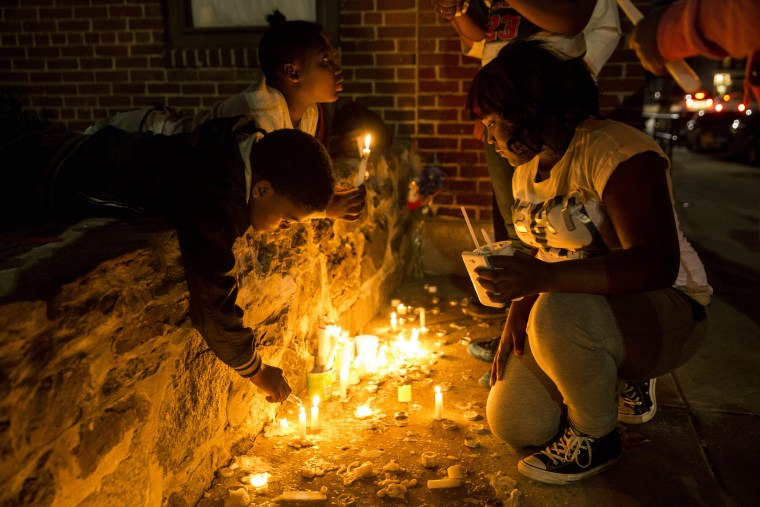 Neighborhood children light candles at a memorial after a march and vigil for Freddie Gray, April 21, 2015 in Baltimore, Maryland. Gray, 25, died from spinal injuries on April 19, one week after being taken into police custody.