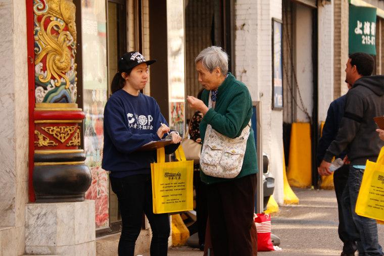 An AAU youth volunteer explaining how to vote to an elder in Philadelphia.