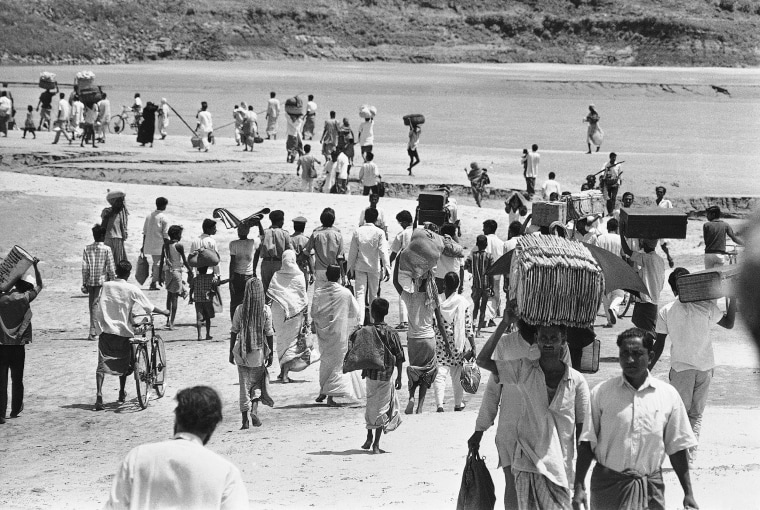 Carrying their few worldly possessions, Bengalis stream across the shallows of the River Ganges Delta at Kushtia, East Pakistan, to escape from the advancing troops of the West Pakistan army fighting near Goaiubogath on April 8, 1971.