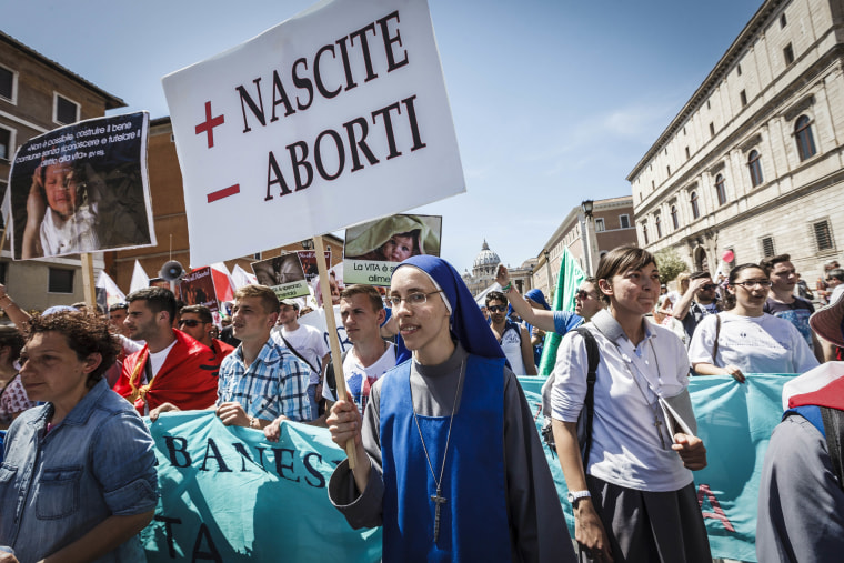 "Image: A nun holds a placard reading ""More Births Minus Abortions"""