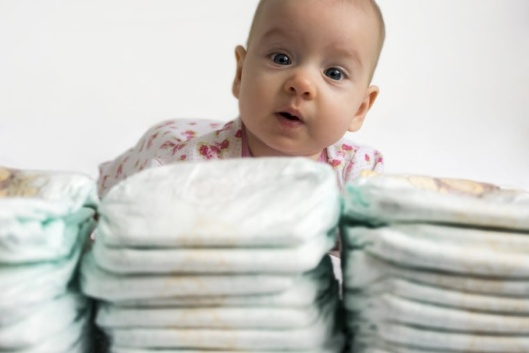 baby looking over a stack of diapers