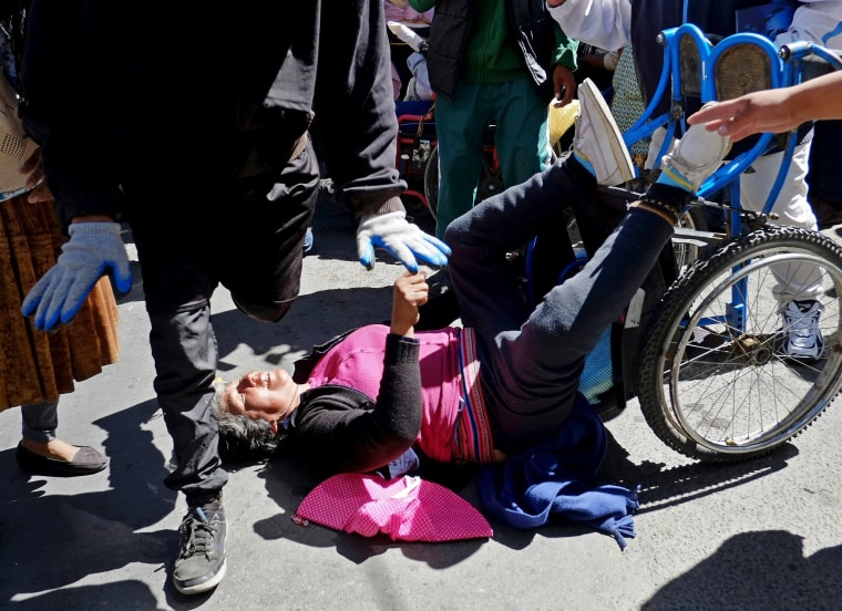 Image: A demonstrator with physical disability falls from a wheelchair during a protest to demand that the government increase the monthly disability subsidy in La Pazwith physical disabilities
