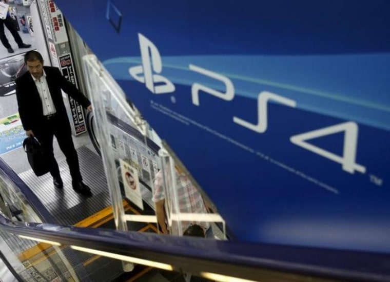A man rides an escalator under a advertisement board of Sony Corp's PlayStation 4 game console at an electronics retailer in Tokyo