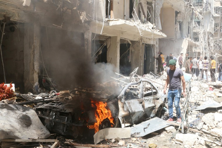 Image: People inspect the damage at a site hit by airstrikes, in the rebel-held area of Aleppo's Bustan al-Qasr