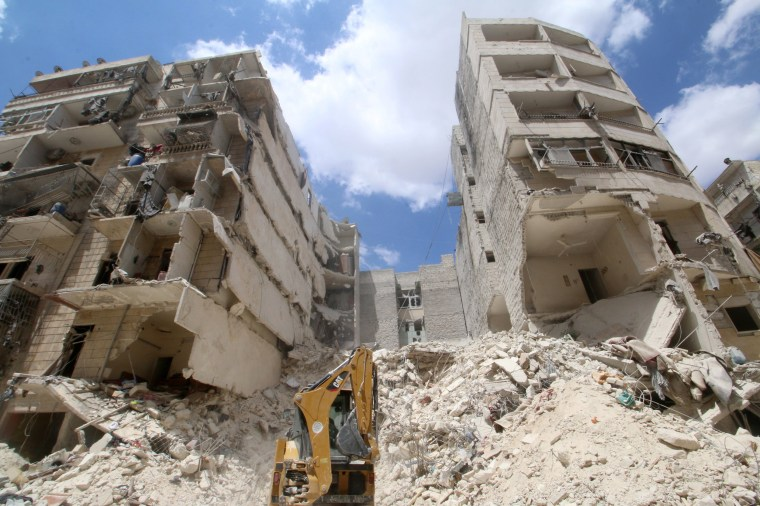 Image: A front loader operates at a site hit by airstrikes in the rebel held area of al-Sukari district of Aleppo