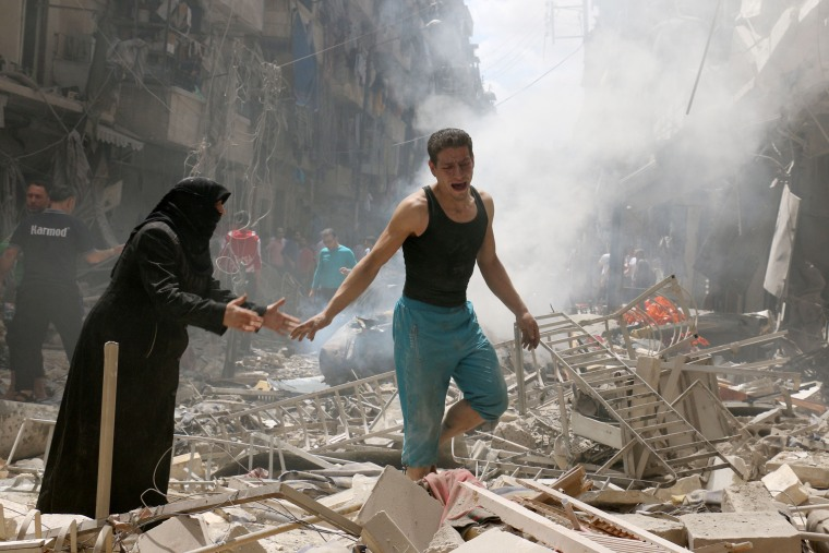 Image: People walk amid the rubble of destroyed buildings  in Aleppo