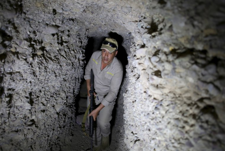 Image: An Iraqi soldier holds his rifle in an underground tunnel built by Islamic State fighters in a village of Har Bardun