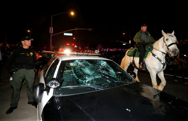 Image: Police on horseback and in riot gear pass by a damaged police car as they break up a demonstration outside Republican U.S. presidential candidate Donald Trump's campaign rally in Costa Mesa