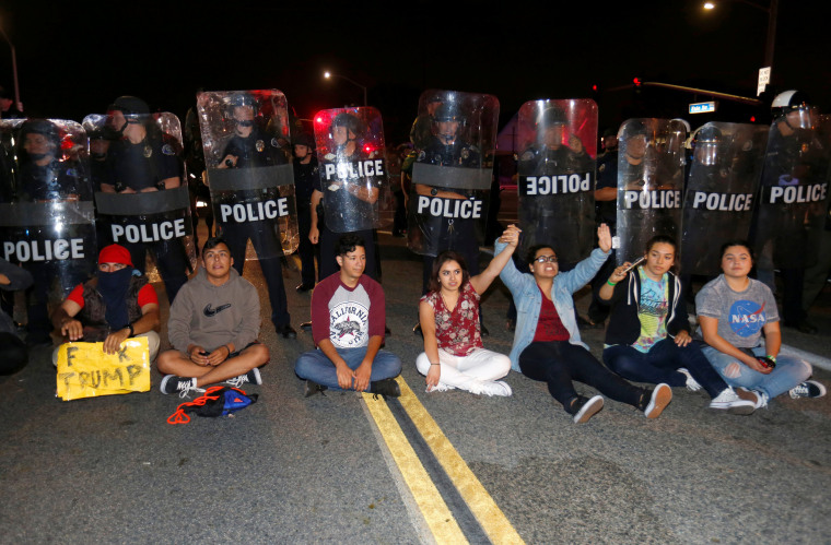 Image: Demonstrators sit in front of a line of police in riot gear outside Republican U.S. presidential candidate Donald Trump's campaign rally in Costa Mesa, California