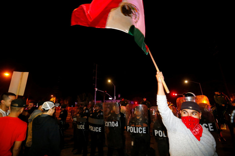 Image: Police in riot gear form a line to begin to break up a group of protesters outside Republican U.S. presidential candidate Donald Trump campaign rally in Costa Mesa