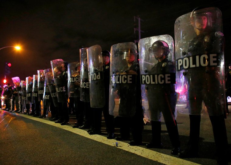Image: Police in riot gear arrive to break-up a demonstration outside Republican U.S. presidential candidate Donald Trump's campaign rally in Costa Mesa
