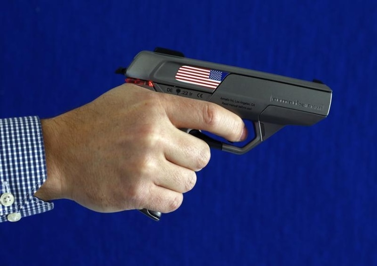 An Armatix employee holds a smart gun by the company at the Armatix headquarters in Munich