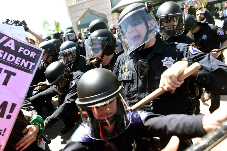 Image: Police in riot gear hold back demonstrators against Trump outside the Hyatt hotel where Trump is set to speak at the California GOP convention in Burlingame, California