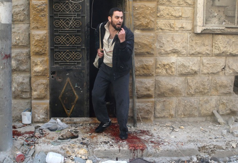 Image: A man reacts as he stands on blood stains at a site hit by airstrikes in the rebel held area of Aleppo's al-Fardous district