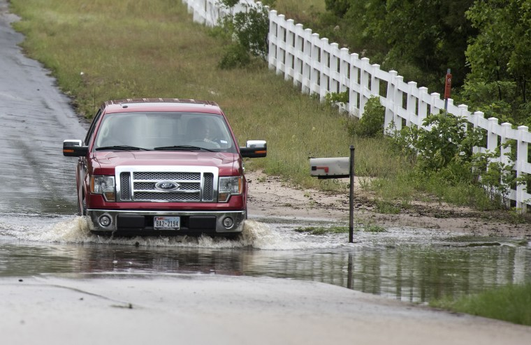 A man drives through floodwaters near the Ozarka Wood County Bottling Plant in Hawkins, Texas, on April 30, 2016. The Ozarka Plant's roof was reported damaged and trucks were reportedly overturned in their parking lot.