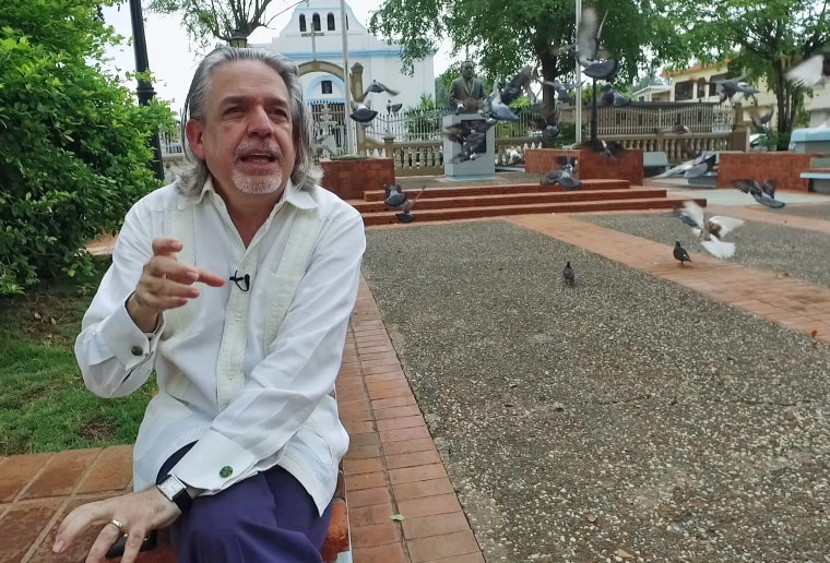 "Lin-Manuel Miranda's father, Luis Miranda, sits in the town square, or ""placita"" in his hometown of Vega Alta, Puerto Rico. Like many, he is extremely worried about the island's spiraling economic crisis."