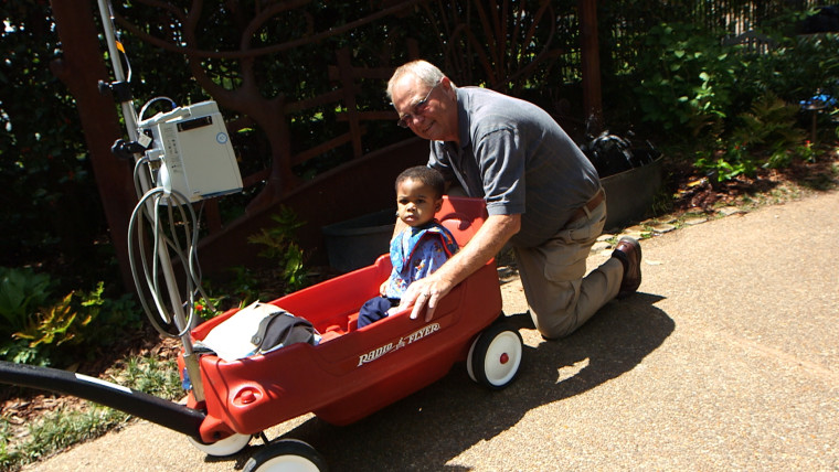 Roger Leggett and Landon in one of Leggett's wagons, designed to help children with medical issues enjoy easier movement. Leggett designed the devices after noticing how difficult it was to move children with IV drips while his granddaughter was in an Atlanta hospital for a brain tumor.