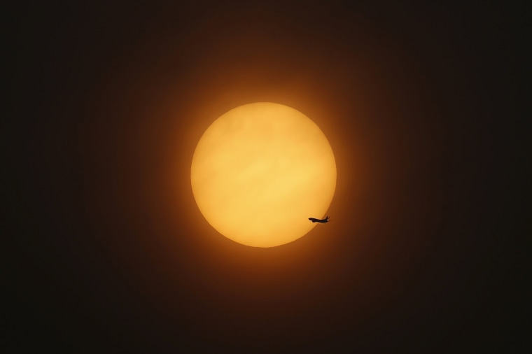 Image: An aeroplane flies past the setting sun near Hongqiao International Airport in Shanghai