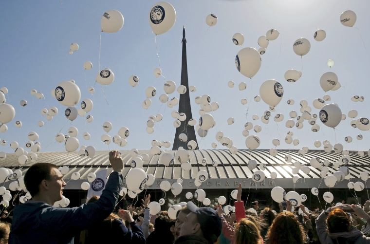 """Image: People release balloons with an image of Yuri Gagarin, the first man in space, during a gathering to mark \""""Cosmonautics Day\"""" near the Memorial Museum of Cosmonautics in Moscow"""