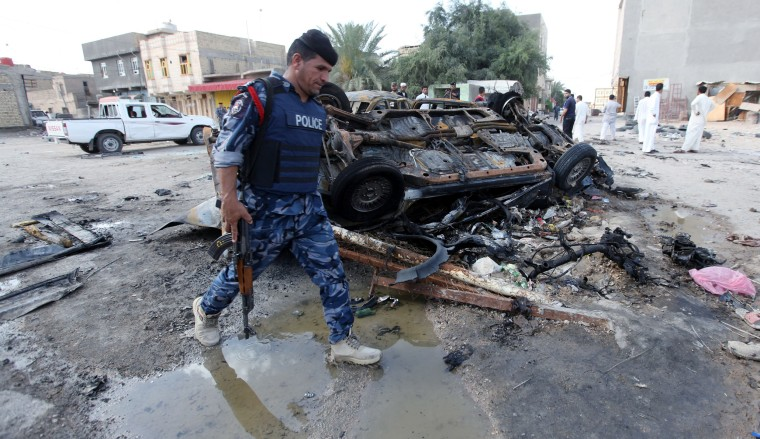 Image: An Iraqi policeman walks past the site of a car bomb attack in Samawa