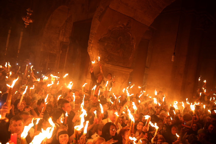 "Image:  Christian Orthodox worshippers hold candles lit from the ""Holy Fire"""