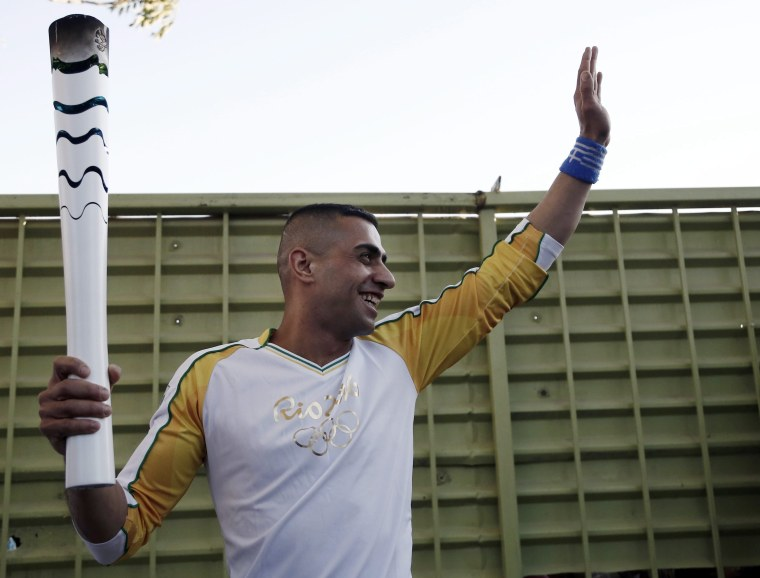 Image: Ibrahim Al-Hussein holds the Olympic torch