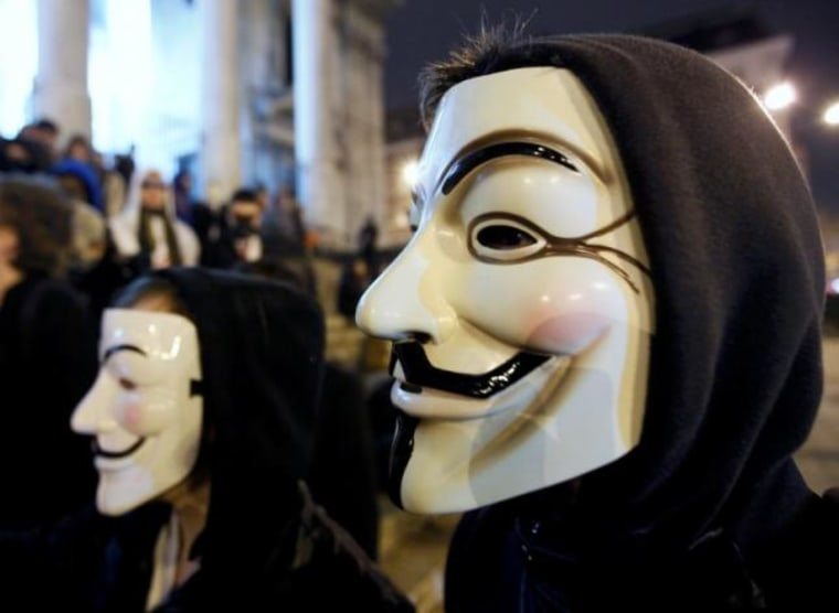 "A protester wearing a Guy Fawkes mask, symbolic of the hacktivist group ""Anonymous"", takes part in a protest in central Brussels"