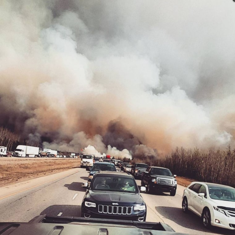Evacuating motorists flees a 10,000-square-mile wildfire on May 3, 2016, near Fort McMurray, Alberta, Canada.  The entire population of the Canadian oil city of Fort McMurray was evacuated overnight as authorities battled an out-of-control wildfire that was likely to worsen again Wednesday.