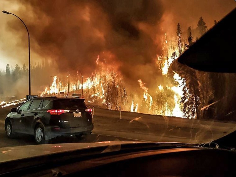 Fires burn at the edge of the road as evacuating motorists flee Fort McMurray on May 3.  There were long lines on highways out of the city of 61,000 people as frantic residents fled the blaze, and oilsands work camps were pressed into service as emergency shelters.