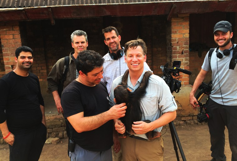 Richard Engel and the team pose for a photo with an orphaned baby chimp outside the headquarters of the conservation rangers' team that saved it in the Democratic Republic of the Congo.