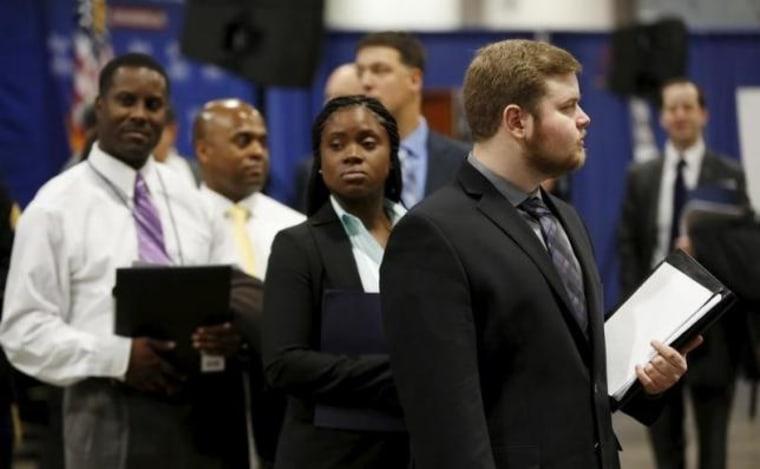 "Job applicants await their turn at the Lockheed Martin booth at ""Hiring Our Heroes"" military job fair in Washington"