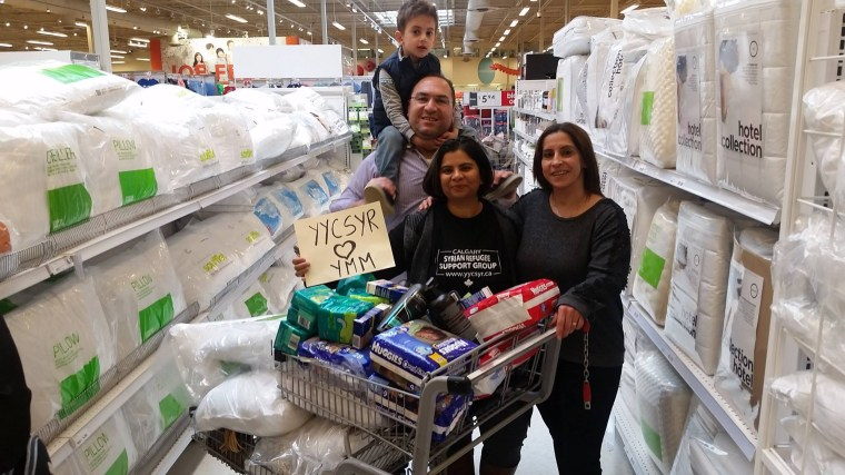"Saima Jamal, right, stands with Syrian newcomers Naser Nader and Rita Khallas as they shop for Fort McMurray evacuees. The sign they're holding up means ""Syrians in Calgary love Fort McMurray."""