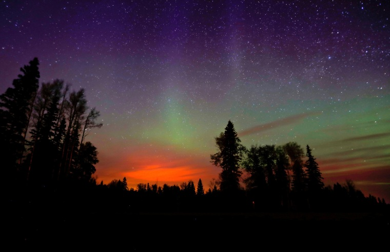 Image: The wildfires glow underneath The Northern Lights