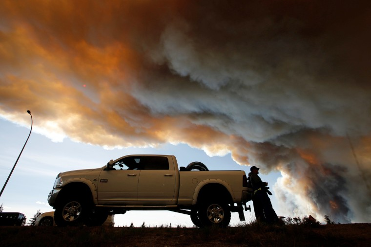 Image: People wait at a roadblock as smoke rises from wildfires near Fort McMurray