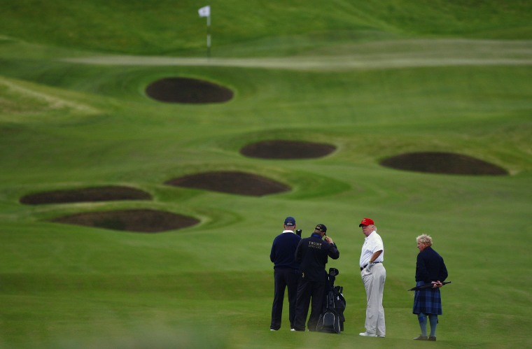 Image: Trump plays golf during the opening of his Trump International Golf Links golf course