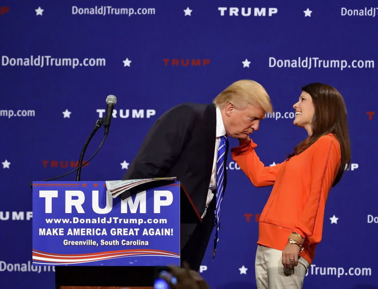 Image: Trump supporter Mary Margaret Bannister checks to see if his hair is real during his speech