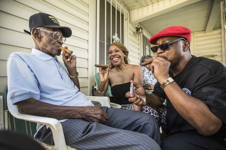 Richard Overton, left,  smokes a cigar with a few neighborhood friends Donna Shorts, center and Martin Wilford Sunday, May 3, 2015, in Austin, Texas.