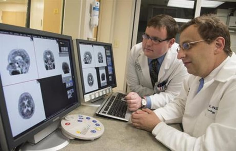 Associate professor of neurology at Washington University School of Medicine Beau Ances MD, PhD, right, and Matthew Brier an MD/PhD student at the university, examining PET (positron emission tomography) scans of Alzheimer's disease patients, in St. Louis. Scientists are peeking inside living brains to watch for the first time as a toxic duo of plaques and tangles interact to drive Alzheimer's disease, with implications for better treatments. (Robert Boston/Washington University via AP)