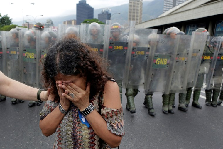 Image: An opposition supporter reacts in front of Venezuelan National Guards in a rally to demand a referendum to remove President Nicolas Maduro in Caracas