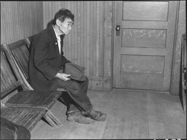 April 25, 1942, Byron, California. Original caption: Toshi Mizoguchi waiting at the Wartime Civil Control Administration station to register for evacuation. Mr. Mizoguchi came to the United States from Japan in 1892 and has been a farm laborer on California ranches since that time. He is unmarried. He is seen wearing an American flag on a celluloid button.