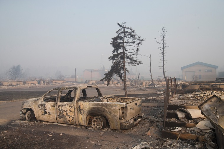 Image: Home foundations and shells of vehicles are nearly all that remain in a residential neighborhood destroyed by a wildfire