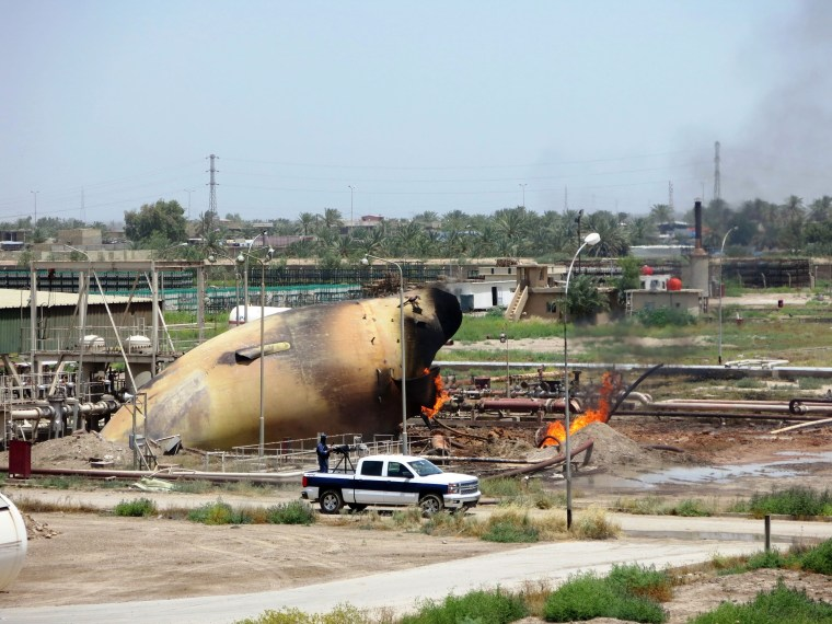 Image: An Iraqi policeman monitors the area next to a burning tank