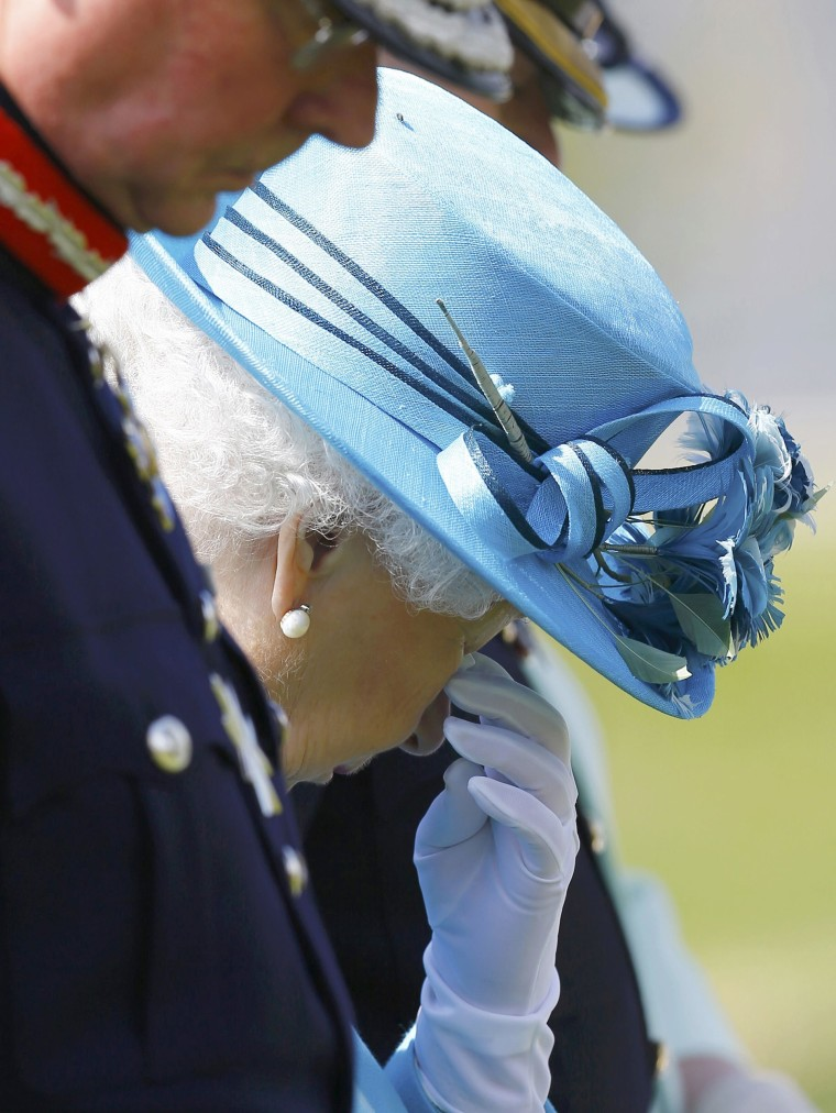 Britain's Queen Elizabeth wiping away a tear while attending dedication of The Lancaster's Regimental Memorial.