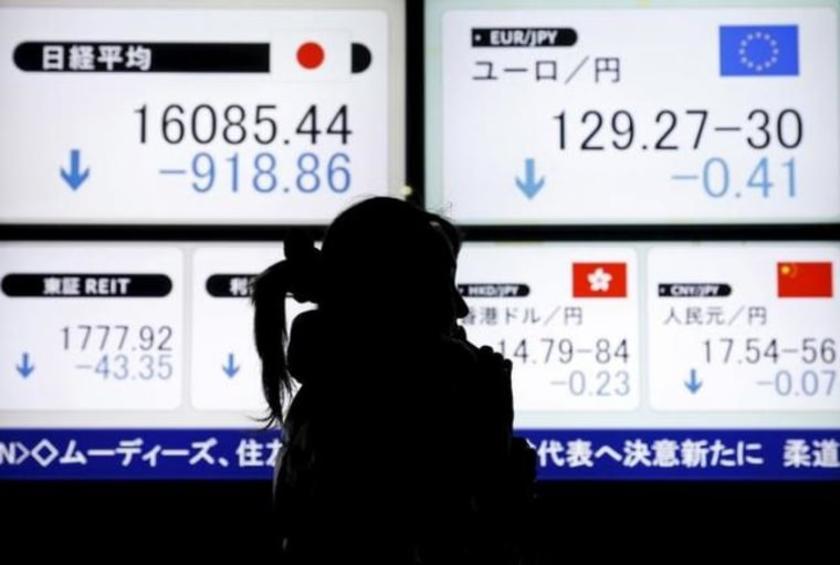 A pedestrian holding her mobile phone walks past electronic boards showing the Japan's Nikkei average and the Japanese yen's exchange rate against the euro outside a brokerage in Tokyo