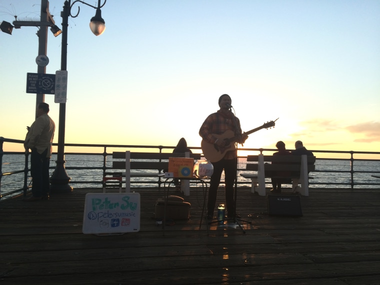 Peter Su, a former investment banker and venture capitalist, busking at the Venice Beach pier in Los Angeles.