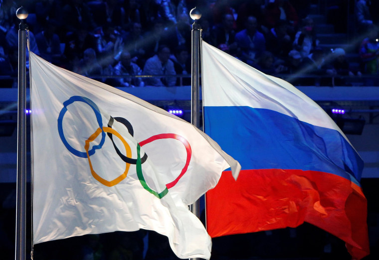 Image: Russian national flag and Olympic flag are seen during closing ceremony for 2014 Sochi Winter Olympics