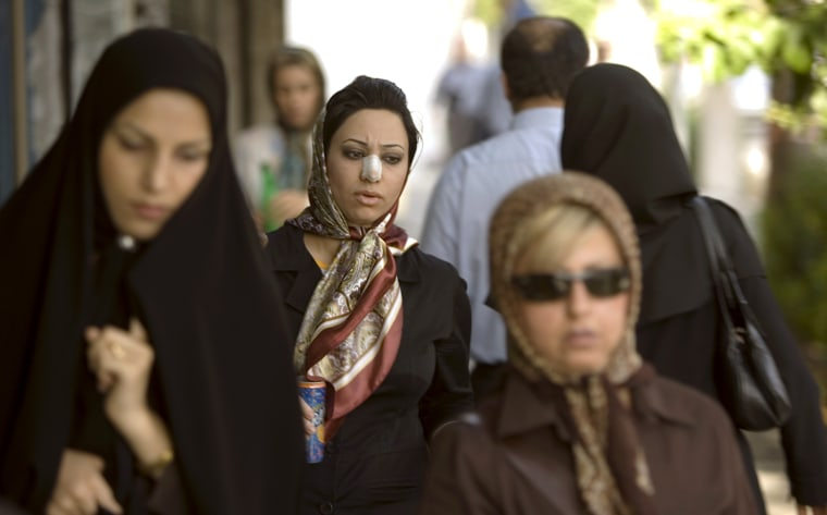 Arezoo Abassi walks along a street in Tehran