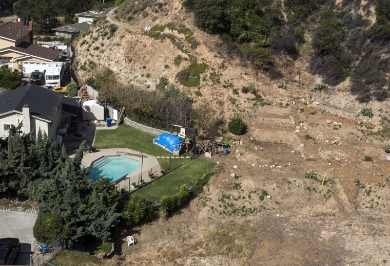 In this April 2, 2015, file photo, a home with a swimming pool sits near a dried out hillside in Altadena, Calif.
